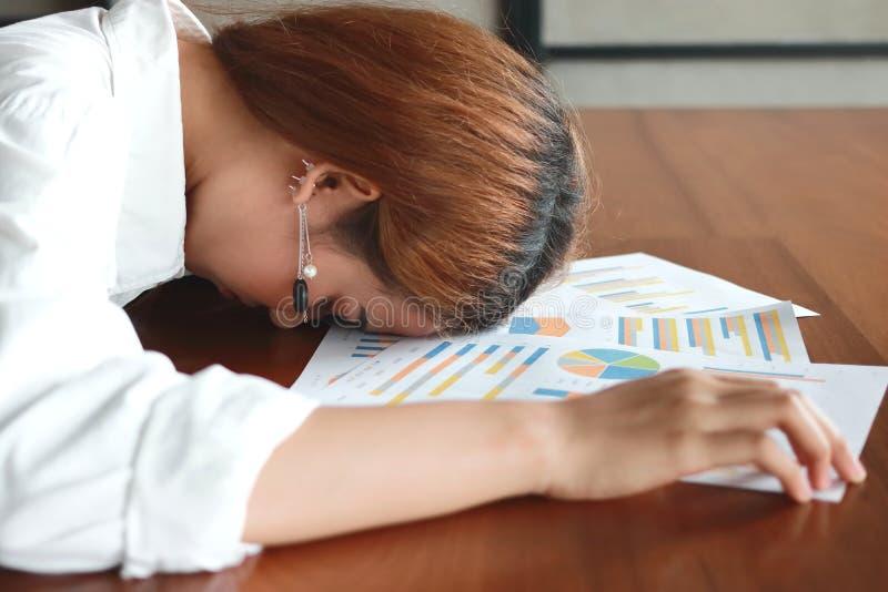 Zachte nadruk van vermoeide overwerkte jonge bedrijfsvrouwenkromming onderaan hoofd op grafieken in bureau stock fotografie
