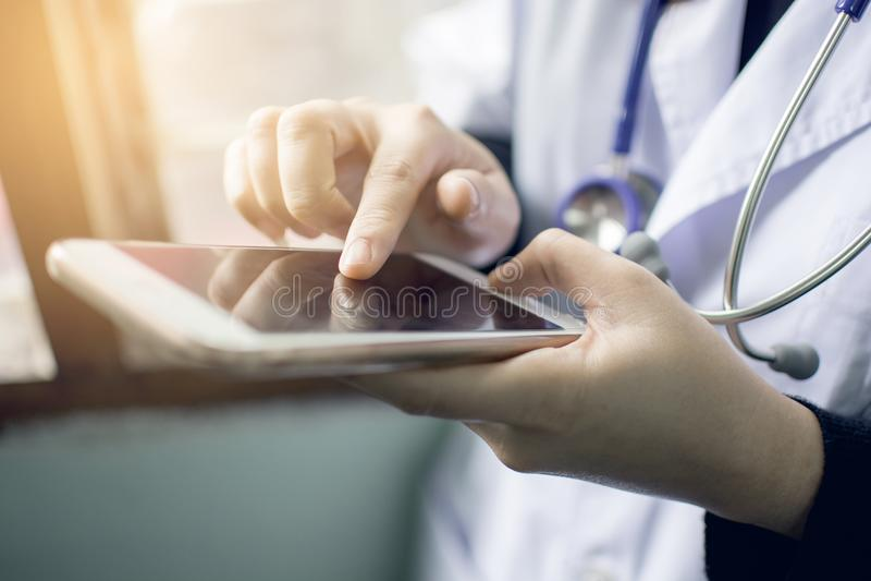 Zachte nadruk van vrouw de holding van de artsenhand en wat betreft het lege scherm voor het werk aangaande moderne slimme telefo stock foto