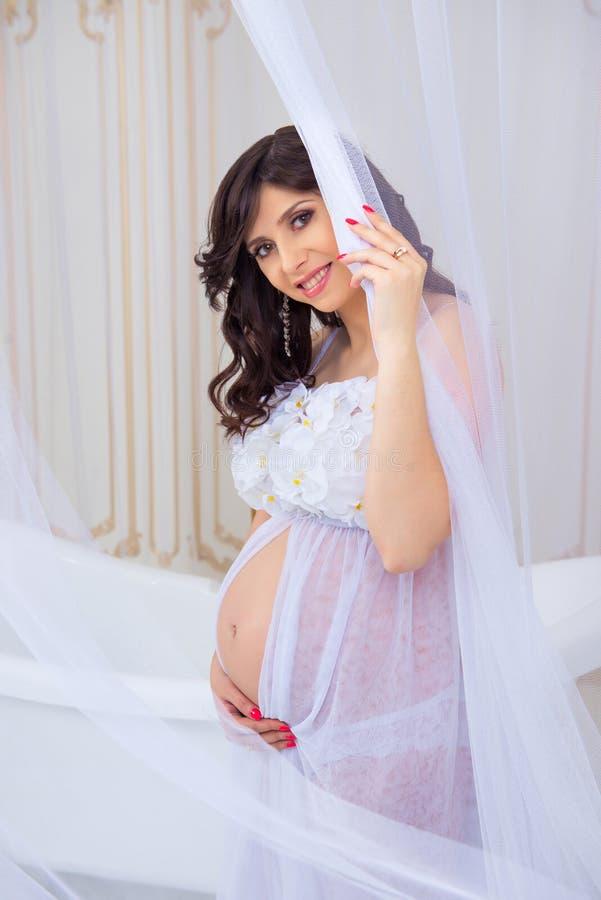 Zachte zwangerschap Mooie zwanger in lichte witte kleding met orchideeën royalty-vrije stock fotografie