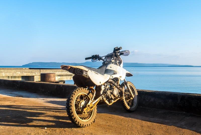Zaczyna podróży pojęcie, Starego Małego Białego motocykl z Błękitnym morzem i niebo w tle, obraz stock