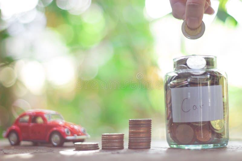Zaczyna stawiającego pieniądze w rocznik szklanej butelce w 2018 monet poj?cia r?k pieni?dze stosu chronienia oszcz?dzanie zdjęcie royalty free