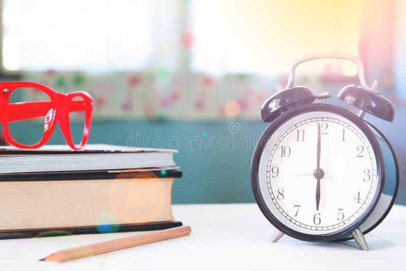Zaczyna up pojęcie, budzika, książki i szkła w ranku, obrazy stock