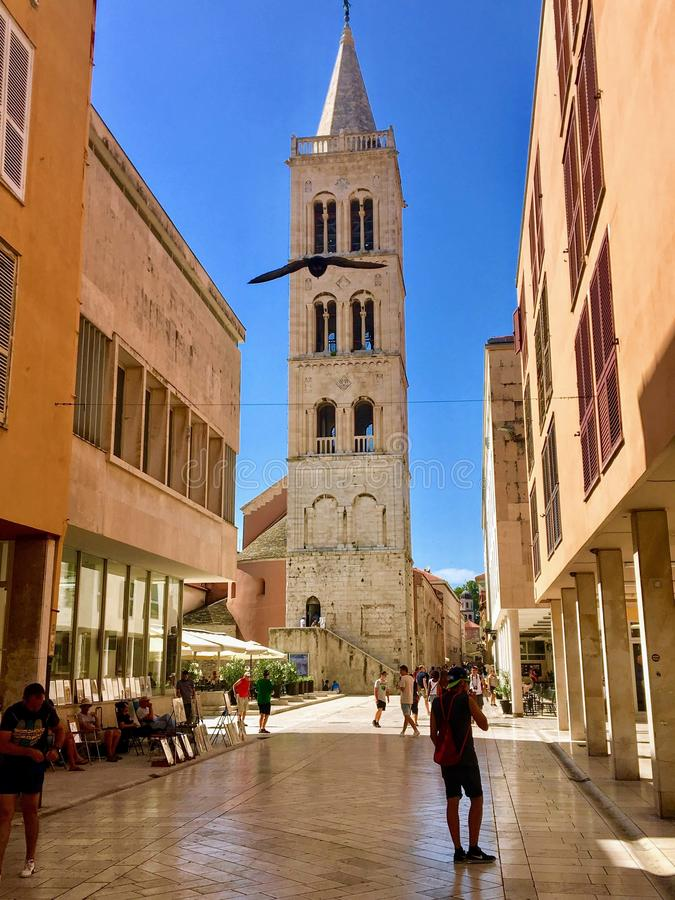 Ourists walking down the main street toward the famous Bell Tower in the old town of Zadar, Croatia. Zadar, Croatia - July 5th, 2019: Tourists walking down the stock image