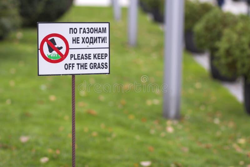 Zadawala utrzymanie z trawa znaka na zielona trawa zamazującym gazonu bokeh tle na pogodnym letnim dniu Miasto natura i styl życi fotografia royalty free