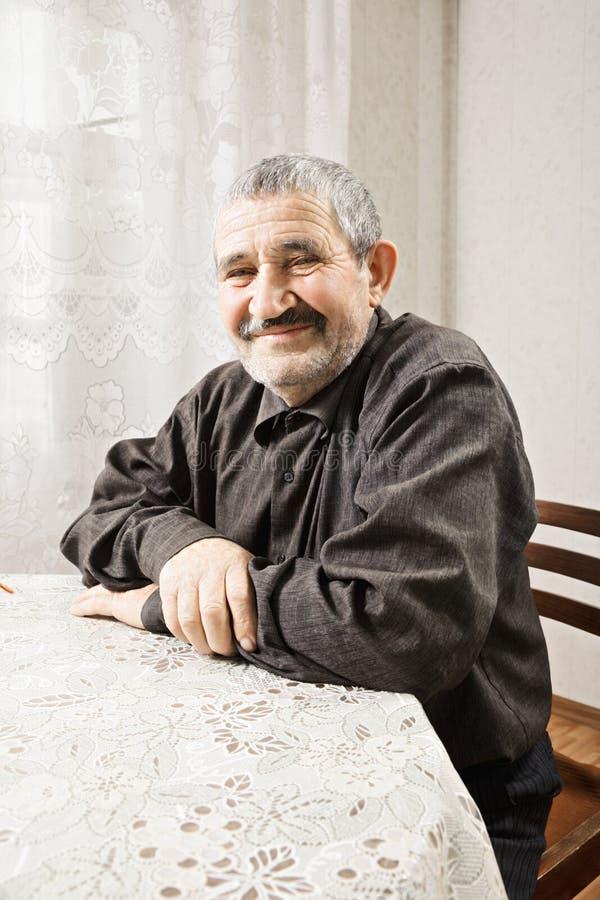 Zadawalający starszy mężczyzna przy stołem obraz royalty free