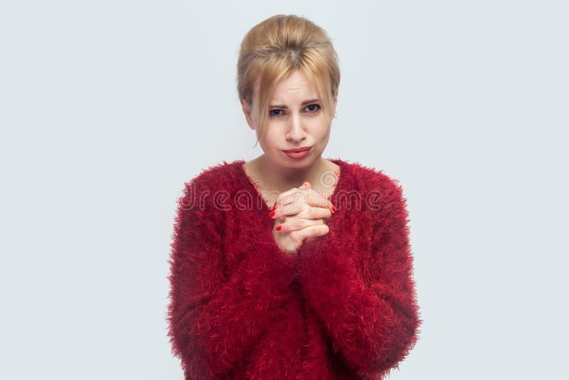Zadawalam wybacza ja lub pomoc, Portret zmartwiona pełny nadziei piękna młoda blond kobieta w czerwonej bluzki pozycji, błagać i  obraz stock