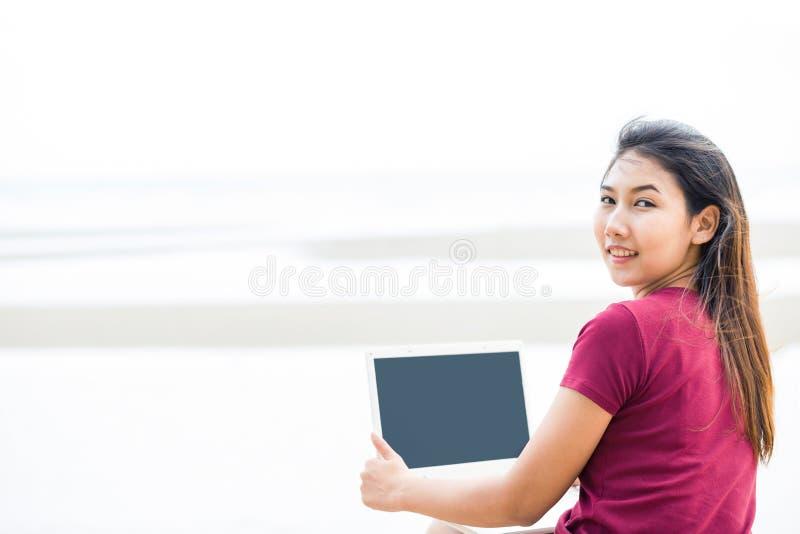 Zadek kobiety i chwyta komputer blisko plaży fotografia stock
