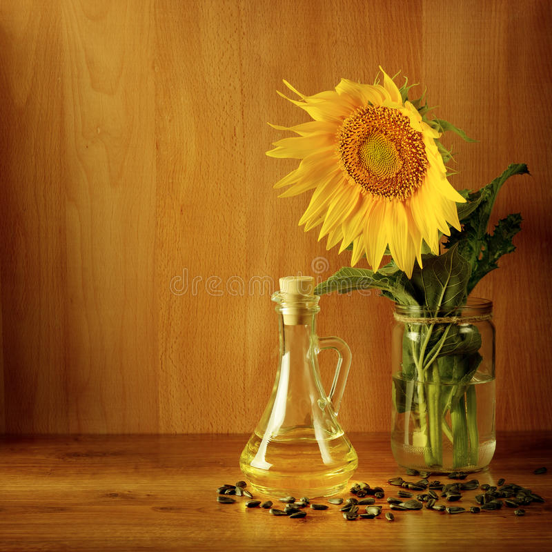 Zaden, olie en zonnebloembloem op houten achtergrond stock afbeeldingen