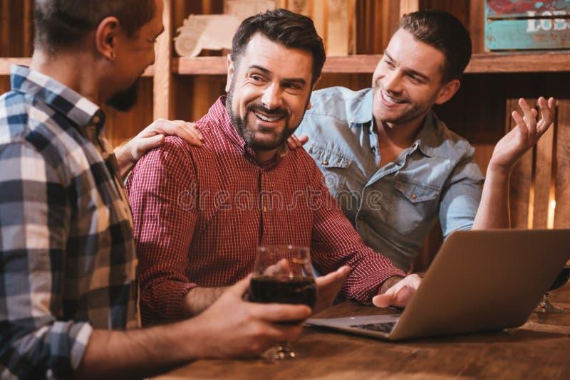 Zadowoleni ładni mężczyzna patrzeje ich przyjaciela fotografia stock