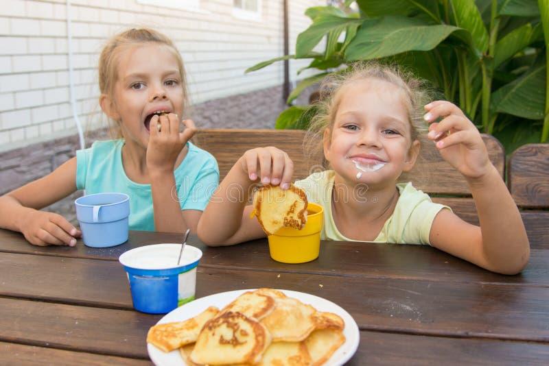 Zadowoleni dzieci przy stołem w podwórzowych łasowanie blinach z kwaśną śmietanką zdjęcia royalty free