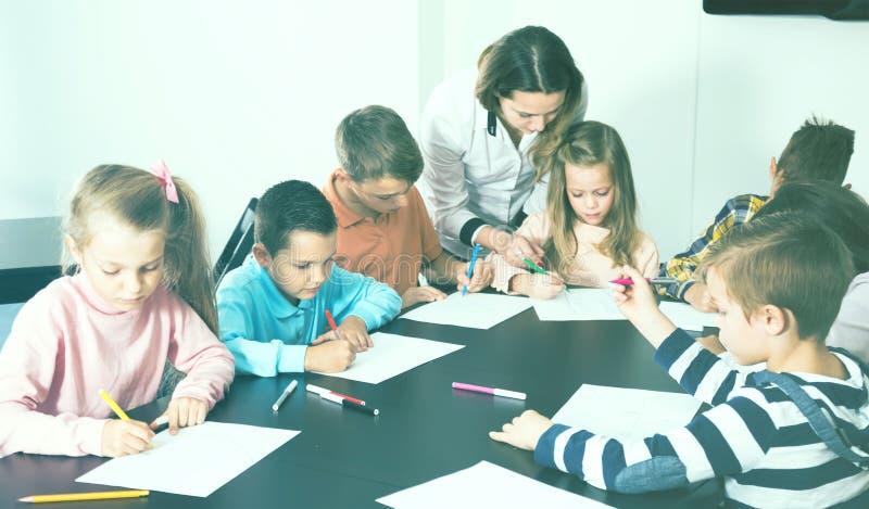 Zadowoleni małe dzieci z nauczyciela rysunkiem w sala lekcyjnej obrazy stock