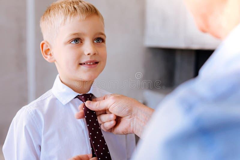 Zadowolona ładna chłopiec ma jego wiązać niezmiennego obrazy stock