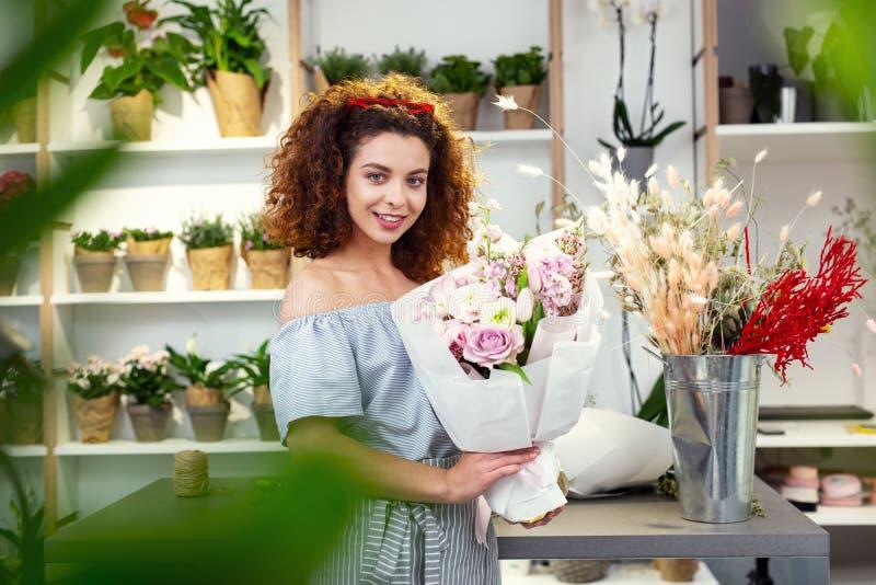 Zadowolona ładna kobieta odwiedza kwiatu sklep zdjęcia stock