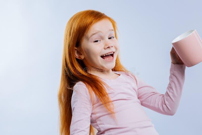 Zadowolona śliczna dziewczyny pozycja z różową filiżanką fotografia stock