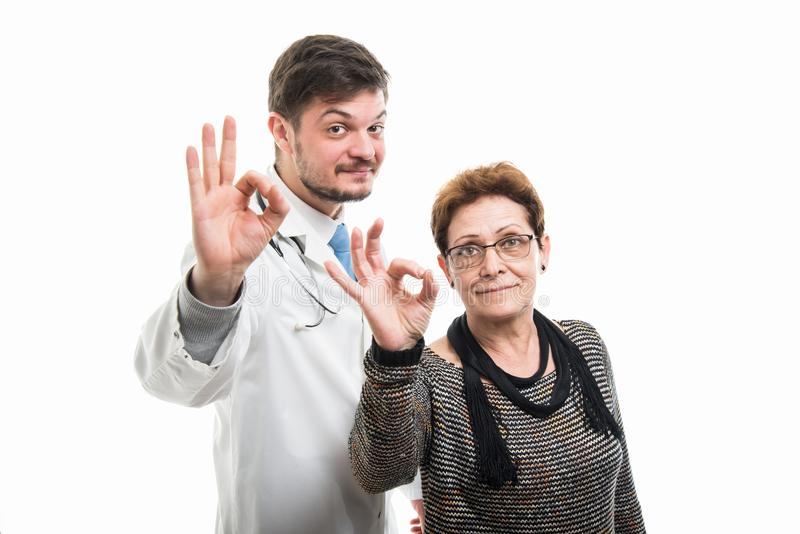 Zadowolona żeńska starsza pacjenta i samiec lekarka pokazuje ok zdjęcie royalty free