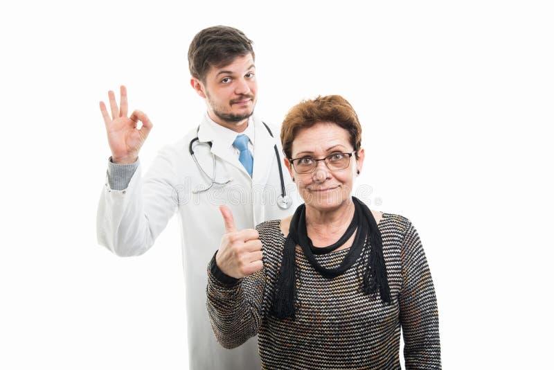 Zadowolona żeńska starsza pacjenta, samiec lekarka pokazuje ok i zdjęcie royalty free