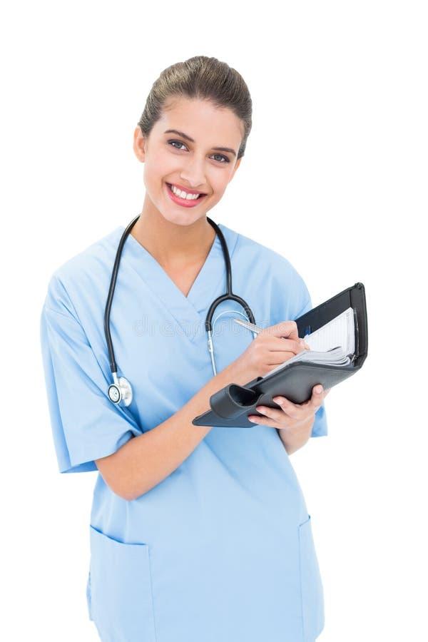 Zadowolona brown z włosami pielęgniarka w błękicie szoruje wypełniać agendę obrazy stock
