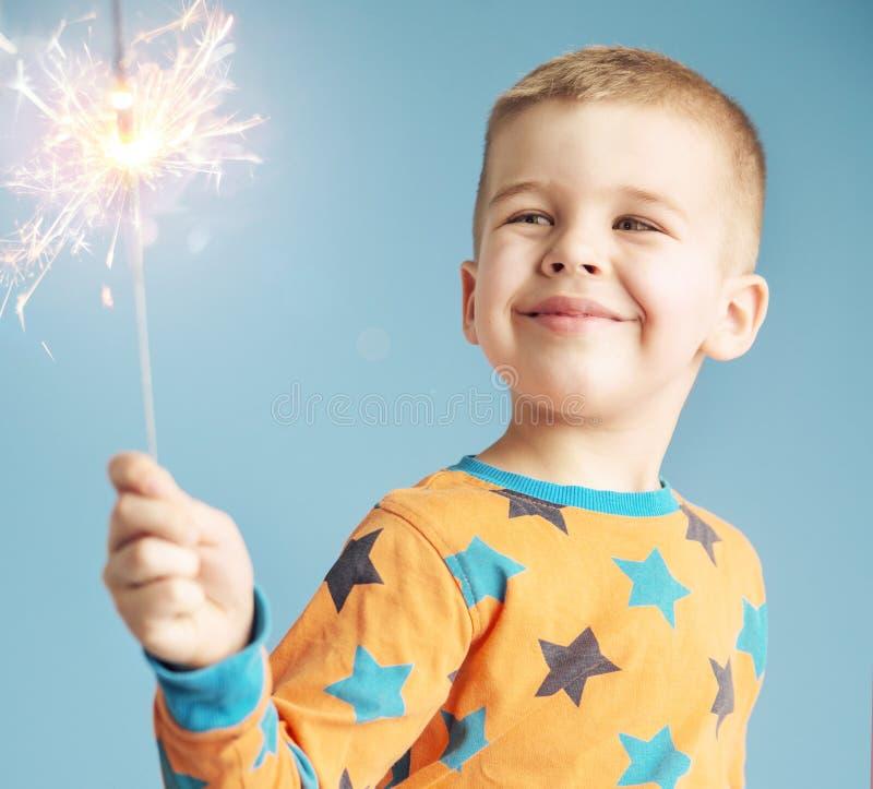 Zadowolona chłopiec ogląda sparkler obraz stock