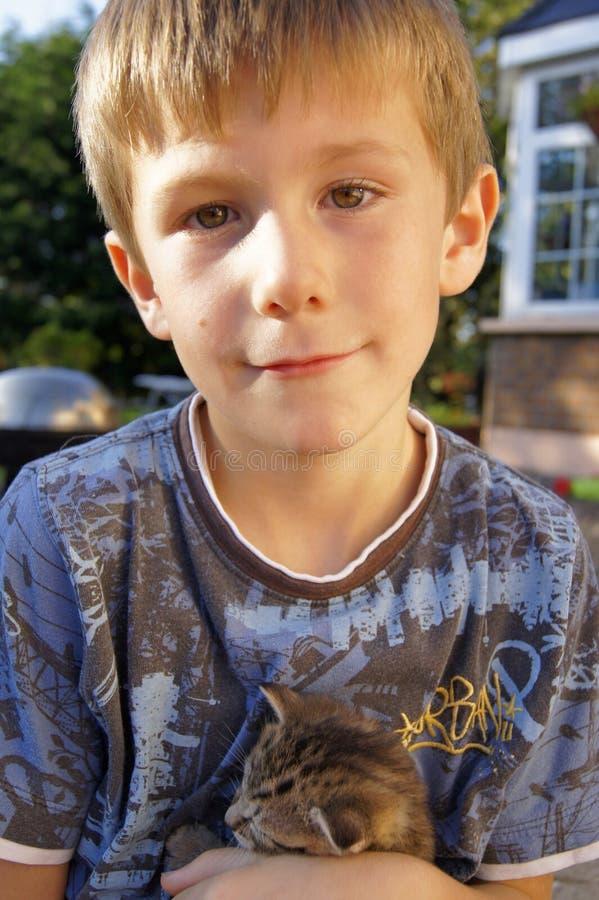 Zadowolona chłopiec outdoors z figlarką zdjęcia stock