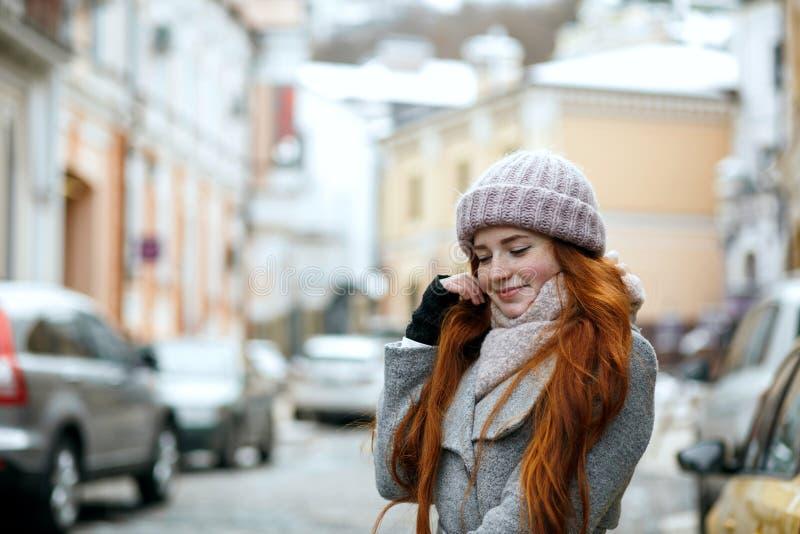 Zadowolona czerwona z włosami dziewczyna jest ubranym ciepłej zimy odprowadzenia odzieżowego puszek fotografia royalty free
