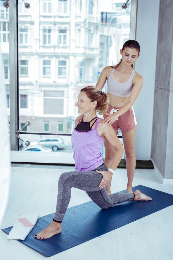 Zadowolona dojrzała kobieta ćwiczy joga z trenerem fotografia royalty free