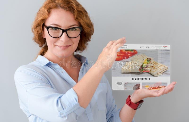 Zadowolona dorosłej kobiety mienia pastylka obraz royalty free