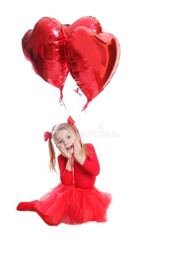 Zadowolona dziewczyna w czerwieni z sercowatymi balonami obraz stock