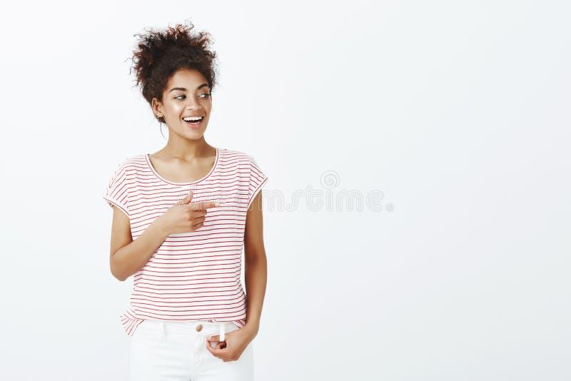 Zadowolona imponująca atrakcyjna kobieta z kędzierzawym rozczesanym włosy wskazuje dobrze z palca pistoletu gestem i patrzeje z, obraz stock