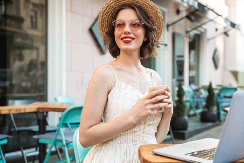 Zadowolona kobieta pije kawę w smokingowym i słomianym kapeluszu zdjęcia stock