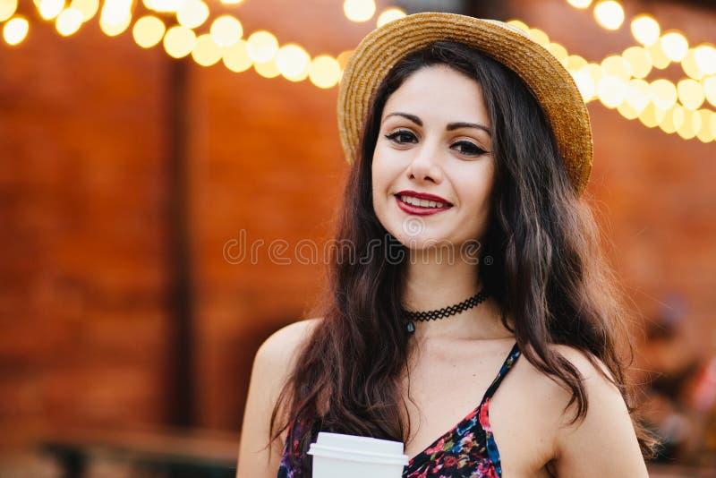 Zadowolona kobieta z czarni włosy, błyszczący oczy i czerwieni wargi, będący ubranym słomianego kapelusz i suknię trzyma takeaway zdjęcia stock