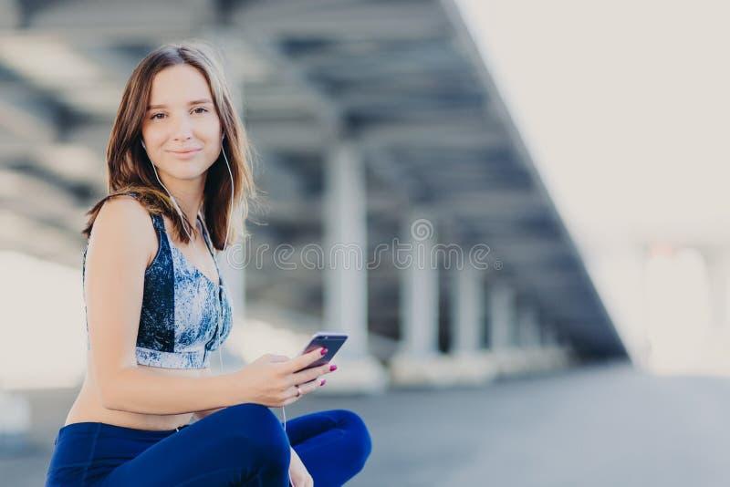 Zadowolona kobieta z zdrową skórą, odczucia odświeżający siedzi w lotosie podczas gdy słucha pupila ślad w słuchawkach, ubierać w obrazy stock