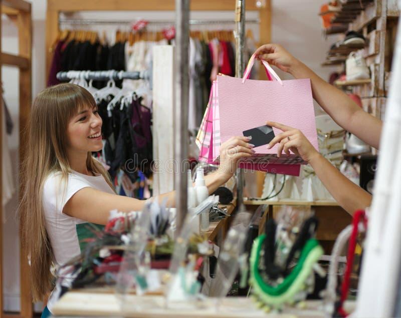 Zadowolona kobiety pozycja w sklepie odzieżowym i płacić dla jej zakupów Shopaholic na zamazanym tle obraz royalty free
