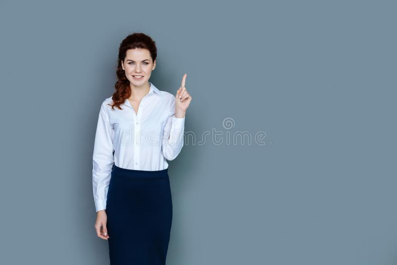 Zadowolona mądrze kobieta wskazuje z jej palcem fotografia stock