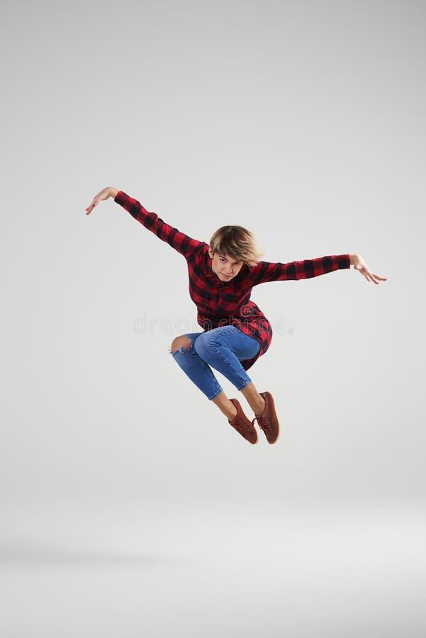 Zadowolona młoda dziewczyna skacze przy studiiem w przypadkowych ubraniach zdjęcie royalty free