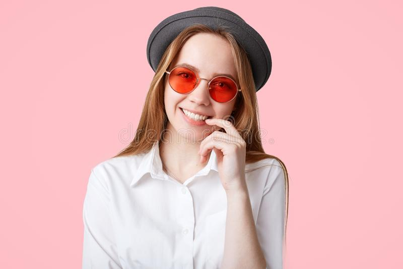 Zadowolona modna modniś dziewczyna z szerokim uśmiechem, jest ubranym modnych okulary przeciwsłonecznych i czarnego kapelusz, poz fotografia royalty free