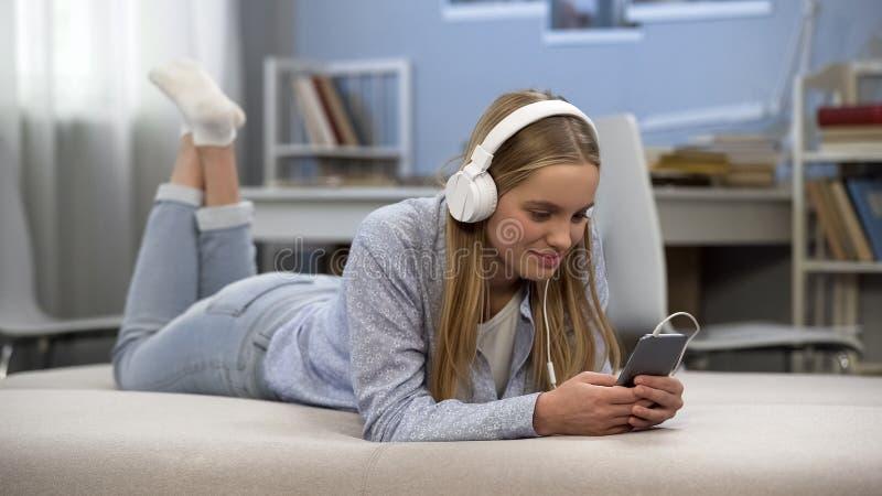 Zadowolona nastoletnia dziewczyna jest ubranym hełmofony, słucha muzyka, relaksu czas obrazy royalty free