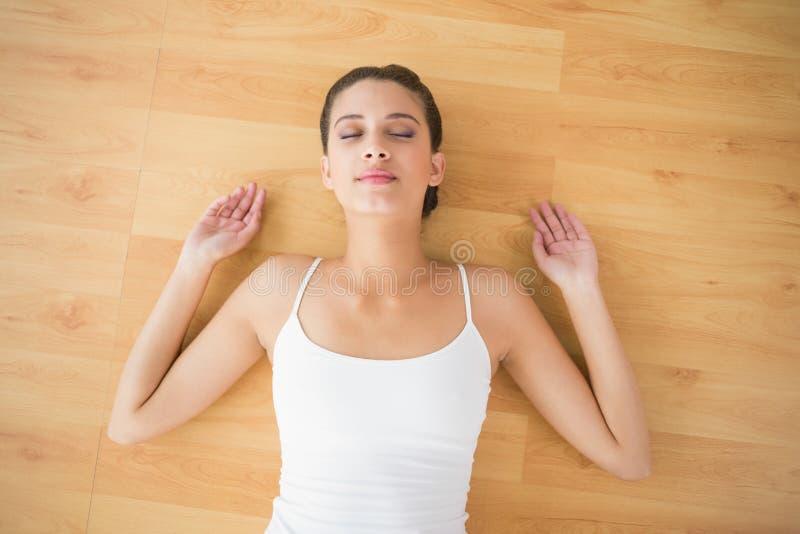 Zadowolona naturalna brown z włosami kobieta w białym sportswear dosypianiu na podłoga obraz royalty free