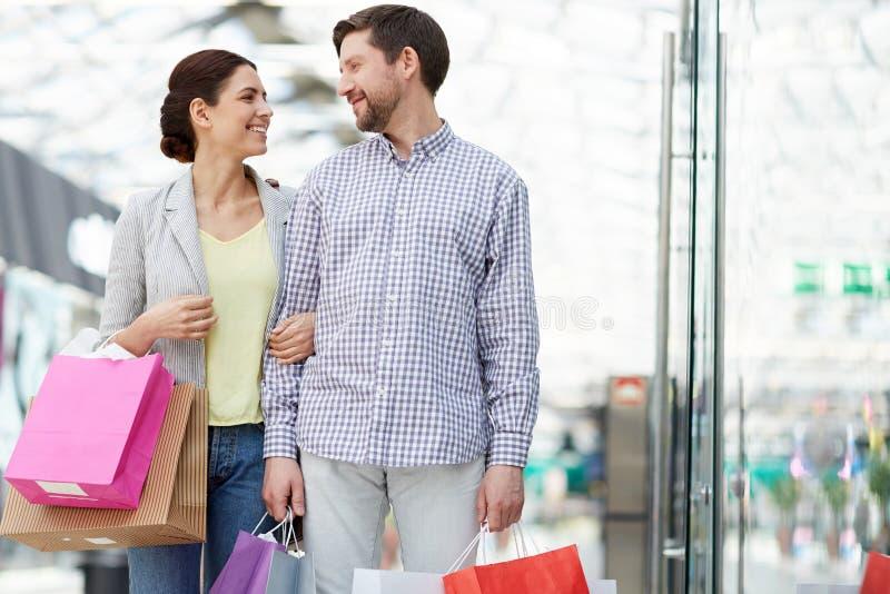 Zadowolona para z torba na zakupy w centrum handlowym zdjęcia stock