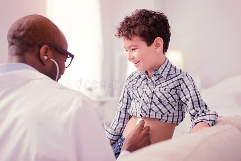 Zadowolona pozytywna chłopiec ma zabawę podczas gdy odwiedzający lekarkę fotografia royalty free