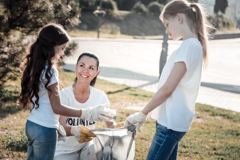 Zadowolona pozytywna kobieta pomaga dzieci fotografia royalty free