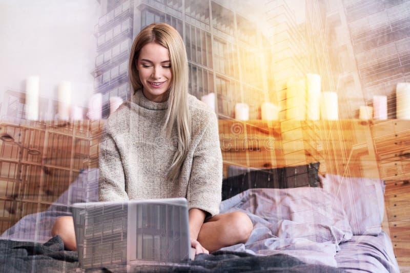Zadowolona pozytywna kobieta pracuje w domu obrazy stock
