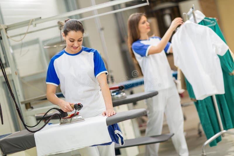 Zadowolona pracownika prasowania tkanina fotografia stock