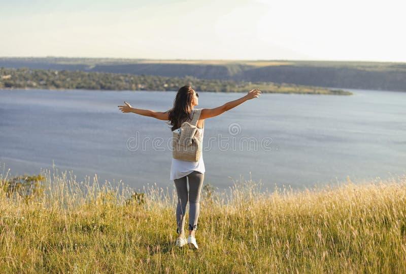 Zadowolona przypadkowa dziewczyna na wysokim jeziora wybrzeżu obrazy royalty free