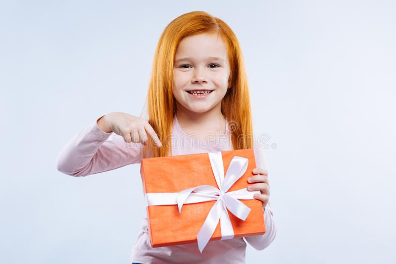Zadowolona rozochocona dziewczyna wskazuje przy prezenta pudełkiem obraz royalty free