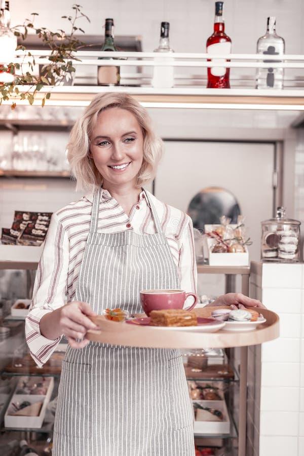 Zadowolona rozochocona kelnerka trzyma tacę z śniadaniem obraz stock