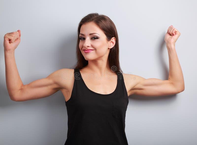 Zadowolona silna młoda kobieta pokazuje mięśni bicepsy z ono uśmiecha się dalej zdjęcia royalty free