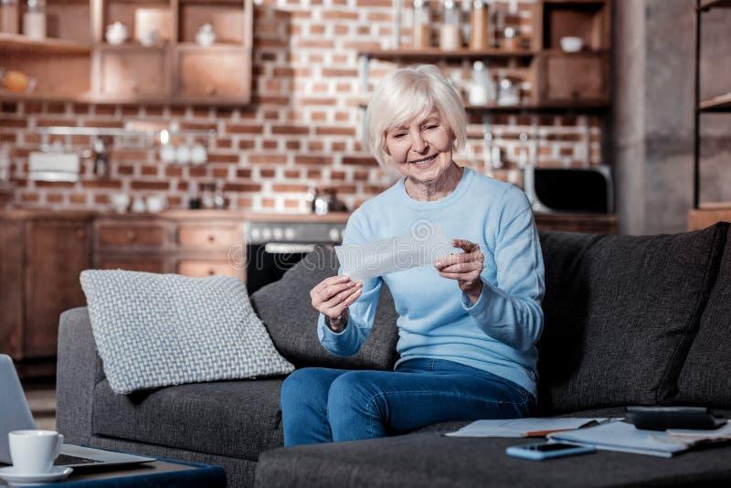 Zadowolona starsza kobieta patrzeje liczenie obrazy stock