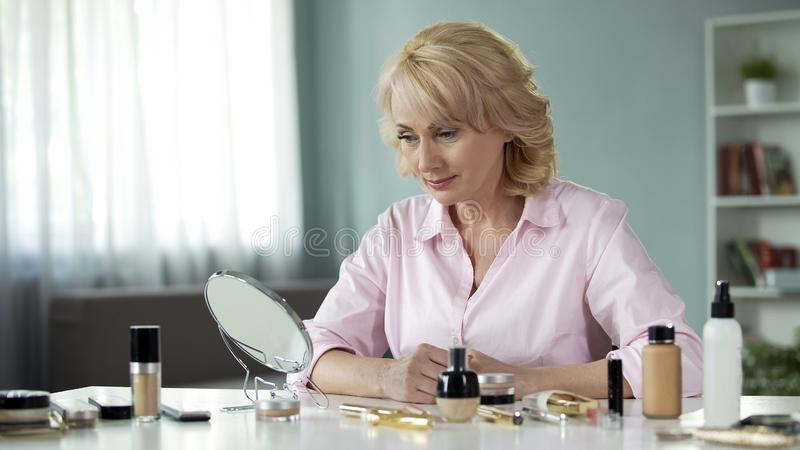 Zadowolona starzejąca się dama patrzeje w małym lustrze, starzenie się kosmetologia, makijaż zdjęcie royalty free