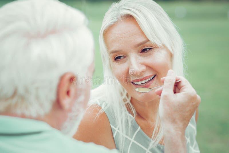 Zadowolona szczęśliwa kobieta karmi jej mężem zdjęcia royalty free