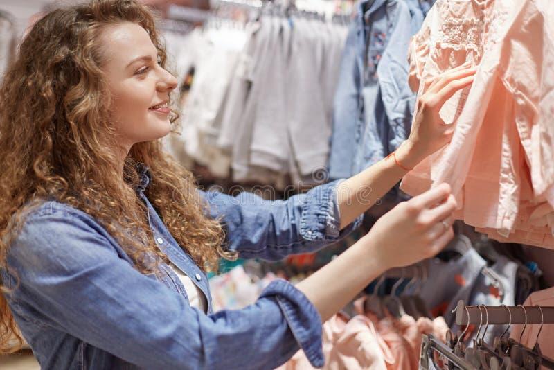 Zadowolona uradowana kobieta z kędzierzawym włosy jest ubranym modną odzież, wybiera nową bluzkę w centrum handlowym, płaci uwagę obrazy stock